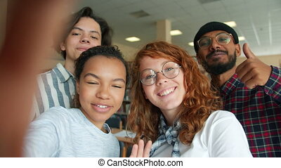 Multi-racial group of young people students is taking selfie in college library smiling showing thumbs-up having fun indoors. Lifestyle and photo concept.