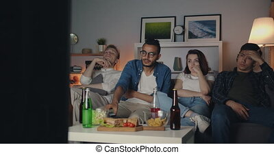 Multi-racial group of young people are watching TV in dark apartment sitting on sofa together yawning using remote control. Entertainment, friendship and modern youth concept.