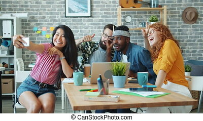 Multi-racial group of coworkers are taking selfie in office room using smartphone posing smiling using smartphone camera. Youth and self-portrait concept.