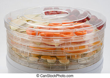 Multi-rack dryer packed with various fruits. Preserving food by drying
