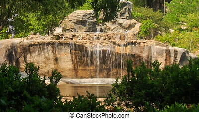 multi-stage waterfall into stone lake in tropical tourist park