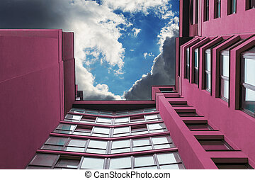 Multi-storey building of purple in the background of the sky with clouds.