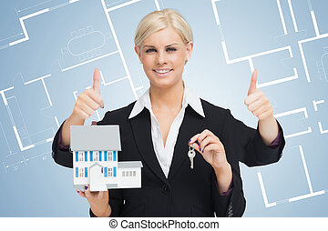 Multi-tasking estate agent holding keys and model home while...