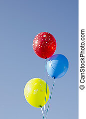 Multicolor balloons tied with strings.