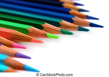 Multicolor bright color pencils diagonal wave on white background with green pencil on focus