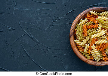 Multicolor spiral macaroni pasta in a wooden bowl on a black textured background from the side. Close-up with the top. With space for text.