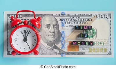 Multicolor text Time is money and red alarm clock walking ticking on background of American hundreds dollar bills, closeup. Concept, Timelapse. Top view.
