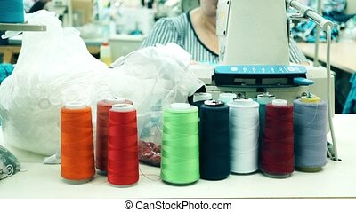 Multicolor thread spools and seamstress at work. Clothing...