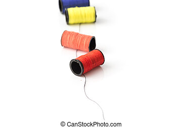 multicolor threads laying on black thread on white background best for sewing idea