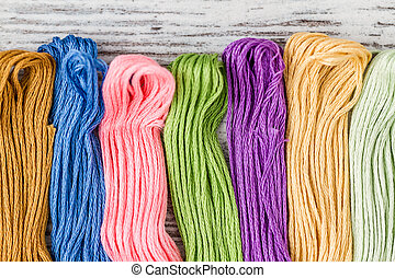 Threads for embroidery from different colors on white wooden background