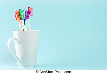 Multicolor toothbrushes in white mug, with copyspace