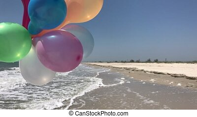 Multicolored balloons against the background of the sea and...