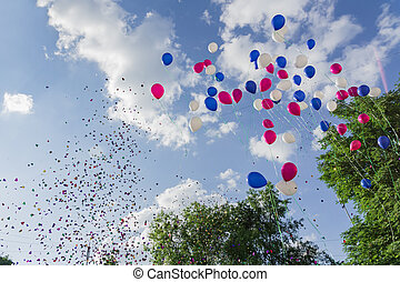 Multicolored balloons and confetti released in the blue sky against background of trees. Festive action