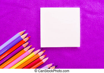 Multicolored, bright, colorful pencils for drawing in the lower left corner and a notebook for your text on a background of purple cloth and space for text