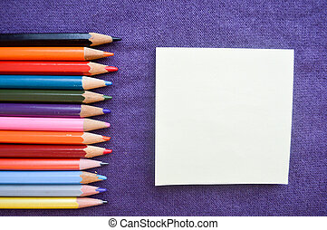 Multicolored, bright, colorful pencils for drawing located on the left and a sheet of paper on the right for your text on a purple background.