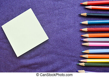 Multicolored, bright, colorful pencils for drawing located on the right and a notebook on the left for your text on a background of purple cloth.