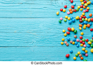 Multicolored candy on wooden table