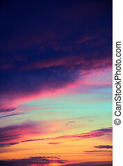 blue, aquamarine, red, orange, yellow, purple, gray clouds in the blue sky during sunset. vertical