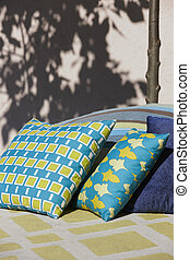 Multicolored cushions in a patio with tree trunk and shadow