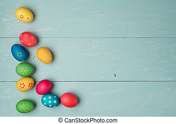multicolored easter eggs on vintage wooden background