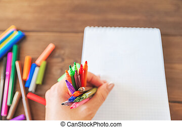 Multicolored felt pens in hand on the background of notebooks on a wooden background. Recreation concept drawing