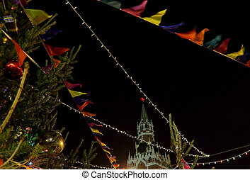 Multicolored garlands of flags and light bulbs against the backdrop of the Spassky Tower of the Moscow Kremlin.