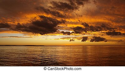Multicolored golden sunrise over water. - Gold,orange and...