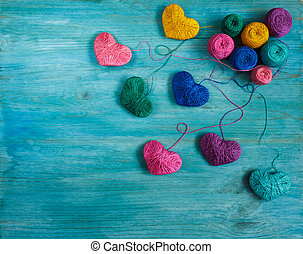 Multicolored Hearts with a balls of thread on blue wooden...