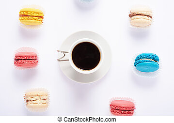 multicolored macaroon and coffee on top of a white background