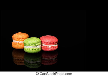 Multicolored macaroons isolated on black background with reflection. Free space for text