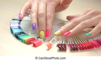 Multicolored manicure and nail polish samples. Young woman...