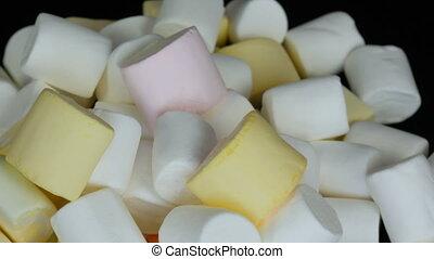 Multicolored mini marshmallow candies rotation slowly on...