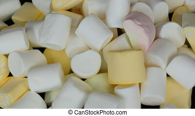 Multicolored mini marshmallow candies rotation slowly on...