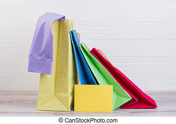 Multicolored paper shopping bags with purchases.