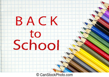 Colored pencils are lying on a white notebook sheet with the inscription back to school