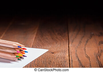 Multicolored pensils on the white paper on a wooden table. Back to school. Copy space.