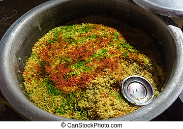 Multicolored rice is the background. Traditional Indian cuisine. Briany in the pot. Cooking street food.