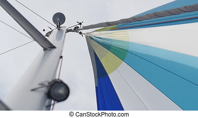 Multicolored Sail blows in wind on a boat.