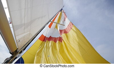 Multicolored Sail blows in wind on a boat. - Multicolored...