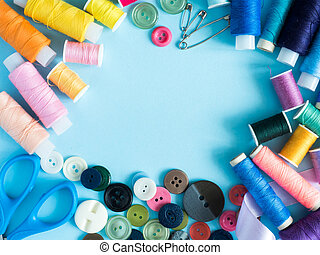 Multicolored sewing threads and buttons on blue background with copy space flat lay