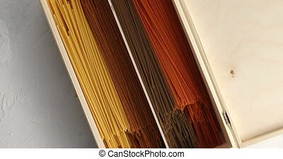Multicolored spaghetti in wood box - From above of wooden...