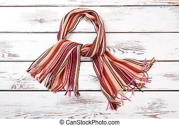 Multicolored striped scarf, wooden background.