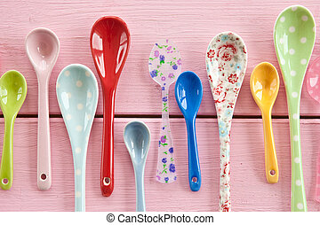 Multicolored tea spoons with various patterns on pink wooden...