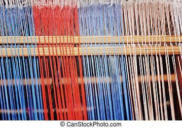 Multicolored thread on a weaving loom taken closeup. Toned ...