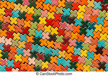 Multicolored tile shape of a cross on the wall.