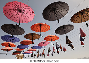 Multicolored umbrellas hanging over head on the street, Yazd, Iran