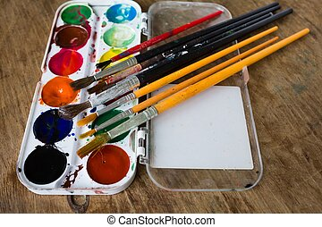 Multicolored watercolor paints and brushes on a wooden table