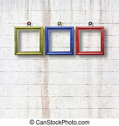 Multicolored  wooden frames for pictures on old stone wall