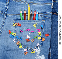 multicolored wooden letters of the English alphabet are scattered on blue jeans
