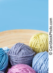 Multicolored woolen balls in bowl. Blue background.